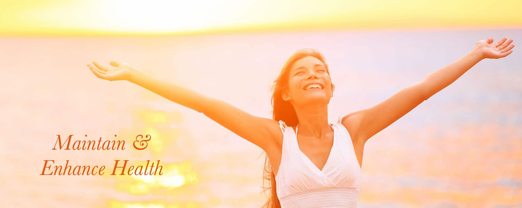 Woman smiling with hands in the air near ocean
