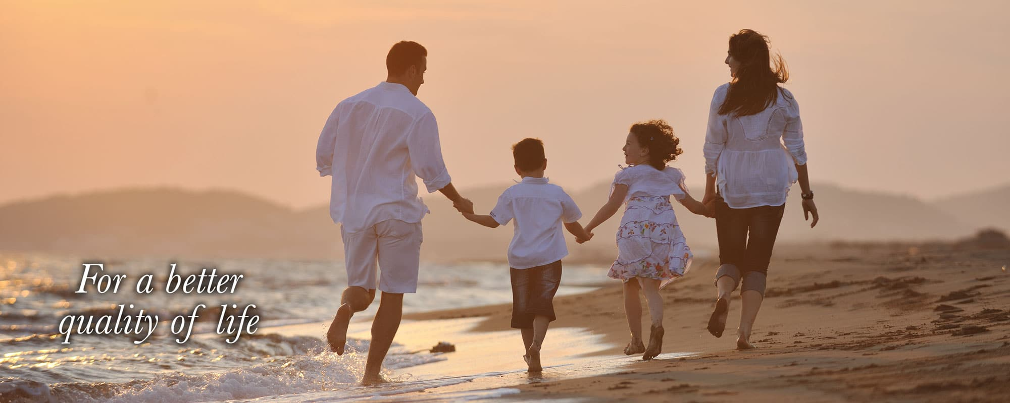 Family of four holding hands running down the beach banner