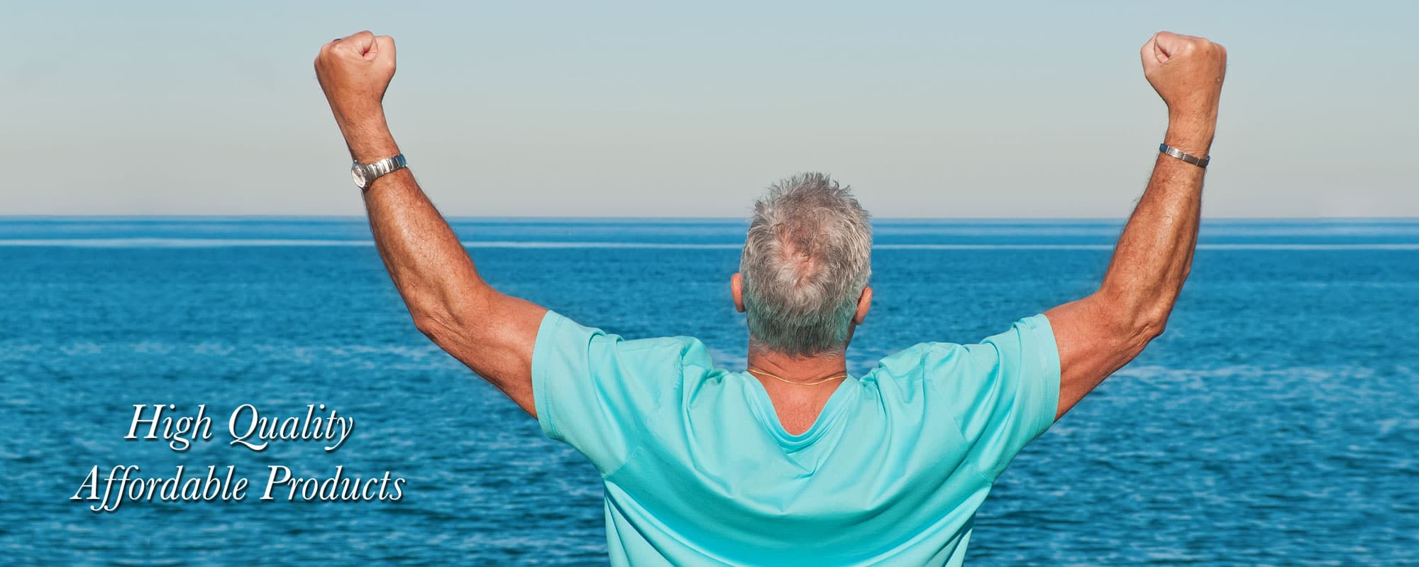 Man Looking at Ocean with his hands in fists in the air
